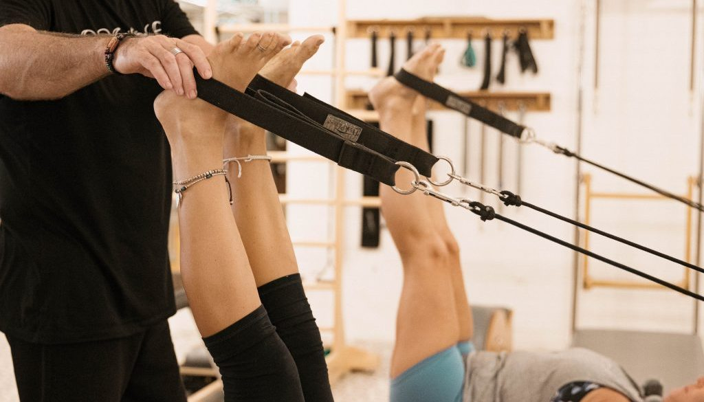 Feet in straps on the Pilates reformer